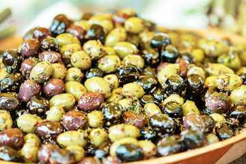 Close-up shot of marinated olives with herbs and spices in wooden plate