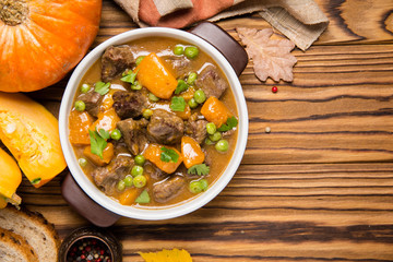 Beef stew with pumpkin, peas and thick sauce, autumn food. Dark bowl on wooden background in rustic style