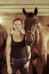 Woman standing next to horse in stable