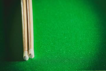 Cue sticks on green billiard table