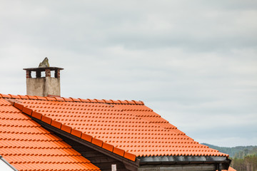 Red roof of house with concrete chimney