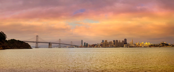 San Francisco CA City Skyline by Bay Bridge during beautiful sunset