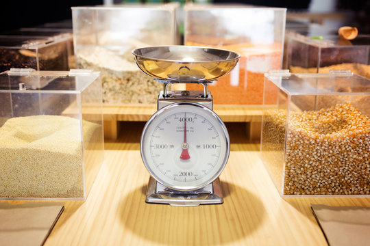 Food weighing machine and different types of condiments in bulk in an organic store.