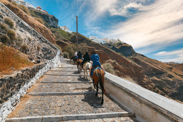 Fotobehang Ezel Tourists on donkeys climb the stairs from the port to the city Fira, modern capital of the Greek Aegean island,Santorini, Greece