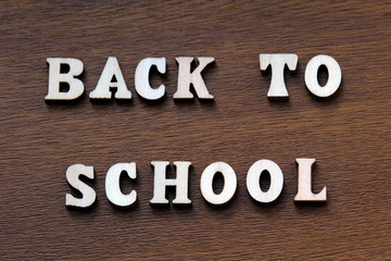 Back to school. Wooden letters on a brown background.