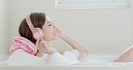 woman listen music in bathtub