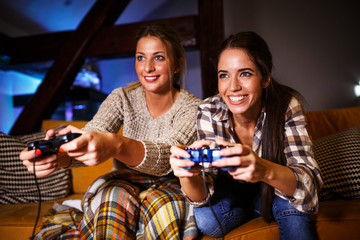 Two female best friends sitting at home on pleasant evening and playing games on console.They challenge each other to win.
