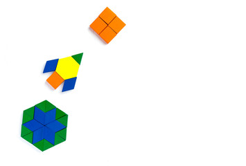 The space ship flies into space to another new planet. Summer happy atmosphere. A child plays with colored blocks constructs a model on a light wooden background.