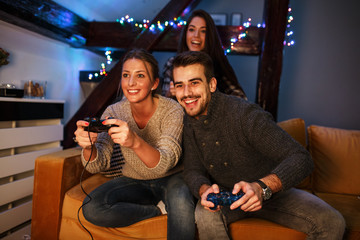 Group of best friends sitting at home on pleasant evening and playing games on console.They challenge each other to win .