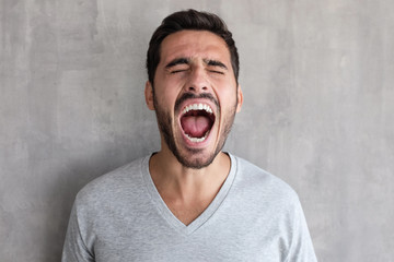 Closeup portrait of screaming with closed eyes crazy young man, standing against gray textured wall