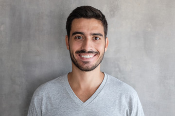 Close up shot of young smiling man standing against gray textured wall