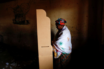 A woman stands at a polling booth before casting her vote inside a polling station during a run-off presidential election in Bamako