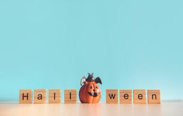 Pumpkin with text Halloween creative idea on table wood and blue wall background, Copy space.