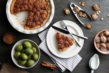 Traditional walnut pie with spices and nuts on dark wooden table, top view