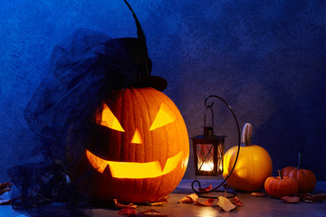 Halloween pumpkin head jack lantern with black bride hat in dark barn, holiday concept