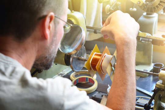 A man producing an electrical copper coil for high-voltage transformer