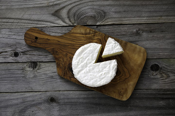 Ripe tasty cheese camembert or brie on a cutting board on an old plank table