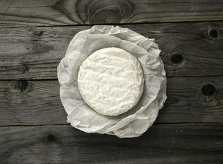 Ripe tasty cheese camembert or brie wrapped in a paper on an old plank table