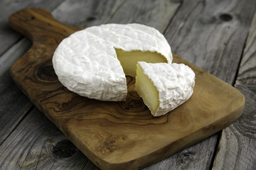 Ripe tasty cheese camembert or brie on a cutting board