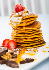 Pancakes served with  fruit, honey, chocolate and whipped cream