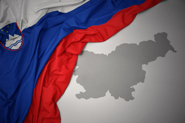 waving colorful national flag and map of slovenia.