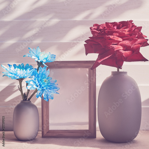 A Large Red Rose Is In A Gray Vase Nearby Is A Bouquet Of Blue