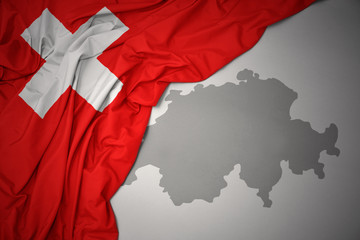 waving colorful national flag and map of switzerland.