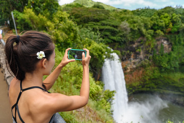 Tourist taking photo pictures of Akaka Falls waterfall on Hawaii, Big Island, USA. Travel tourism concept with multicultural tourist couple.