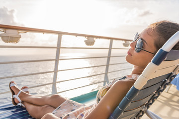 Cruise ship vacation woman relaxing lying on deck lounger at sunset casual lifestyle. Girl enjoying sunshine laid back sleeping on balcony chair on travel summer holidays.