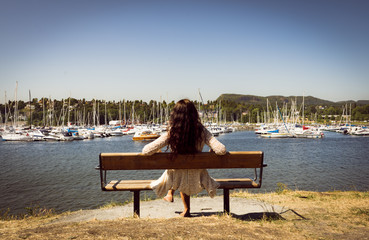 Young woman sitting on a bench in coastal park and watching yachts in the fjord marina