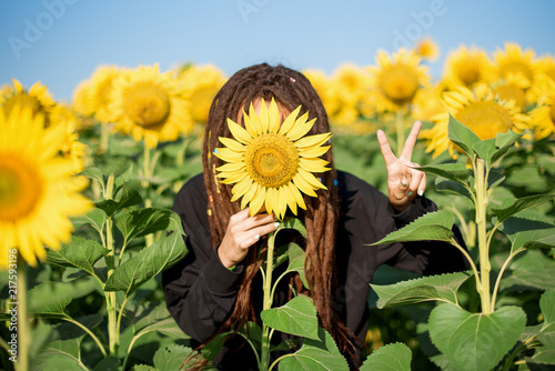 Hippie Girl With Dreadlocks Hides Behind A Sunflower And Shows Peace Sign Summer In