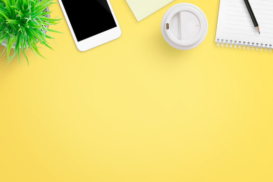 Yellow office desk composition with mobile phone, plant, coffee, notepad and pen. Flat lay.