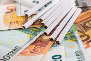 Cigarettes on euro banknotes close up