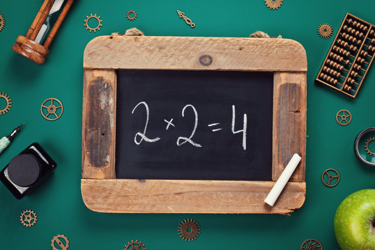 Retro school accessories with math problem on old chalkboard. Back to school concept
