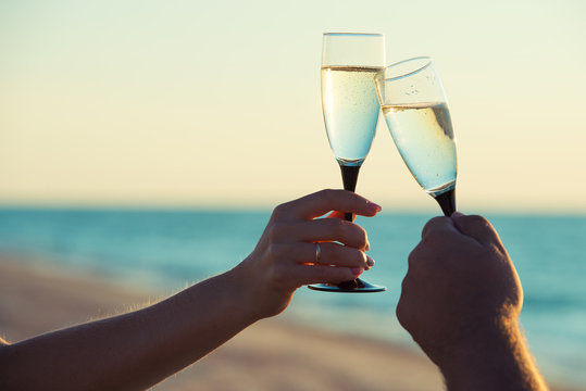 A loving couple drinks champagne on the seashore. Romantic.