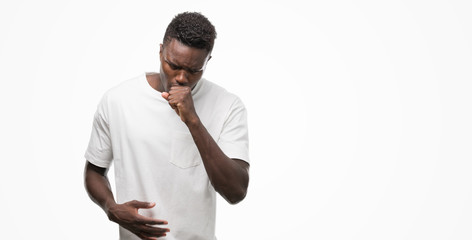 Young african american man wearing white t-shirt feeling unwell and coughing as symptom for cold or bronchitis. Healthcare concept.