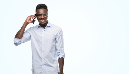 Young african american man using smartphone with a happy face standing and smiling with a confident smile showing teeth