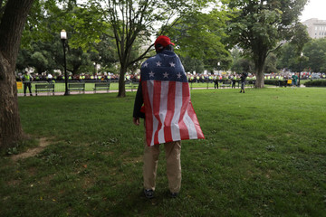 A supporter of white nationalist leader Jason Kessler stands wearing a flag in Washington