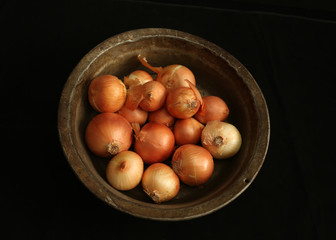 onion in  Copper bowl on black table, top view