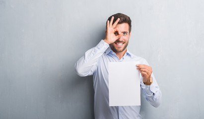 Handsome young man over grey grunge wall holding blank paper sheet contract with happy face smiling doing ok sign with hand on eye looking through fingers