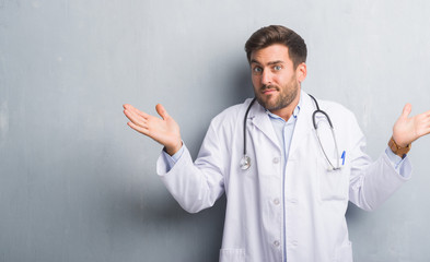 Handsome young doctor man over grey grunge wall clueless and confused expression with arms and hands raised. Doubt concept.