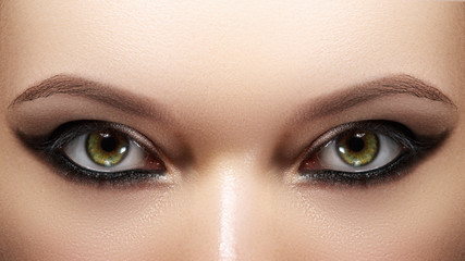 Closeup female eyes with bright make-up, great shapes brows, extreme long eyelashes. Celebrate makeup, luxury eyeshadows