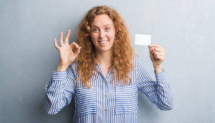 Young redhead woman over grey grunge wall holding blank visit card doing ok sign with fingers, excellent symbol