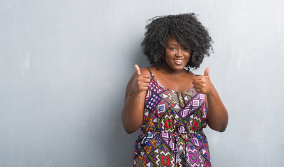 Young african american woman over grey grunge wall wearing colorful dress success sign doing positive gesture with hand, thumbs up smiling and happy. Looking at the camera with cheerful expression.