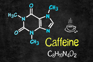 Handwritten chalk chemical formula of Caffeine on school blackboard.