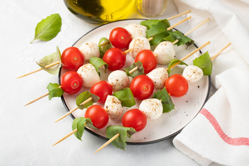 Caprese salad - skewer with tomato, mozzarella and basil, italian food and healthy vegetarian diet concept on a light background