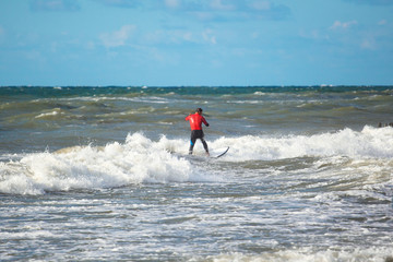 surfer rides on small waves