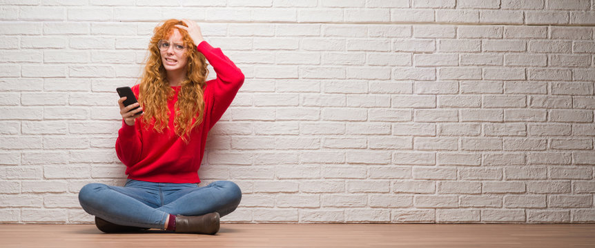 Young redhead woman sitting over brick wall talking on the phone stressed with hand on head, shocked with shame and surprise face, angry and frustrated. Fear and upset for mistake.