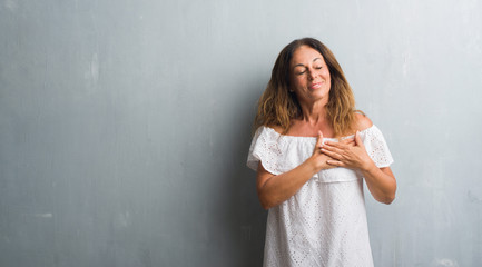 Middle age hispanic woman standing over grey grunge wall smiling with hands on chest with closed eyes and grateful gesture on face. Health concept.