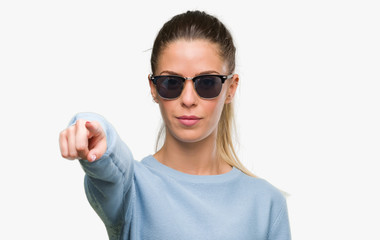 Beautiful young woman wearing sunglasses and ponytail pointing with finger to the camera and to you, hand sign, positive and confident gesture from the front